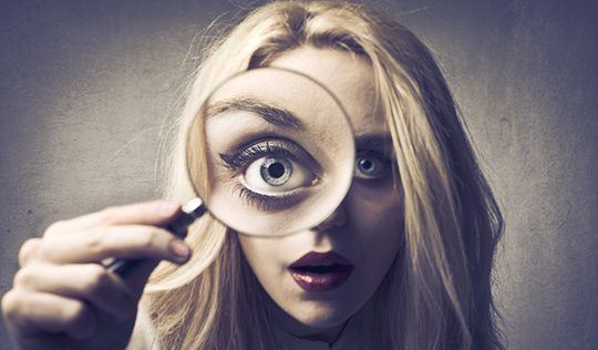 Woman with magnifying glass reading emotions